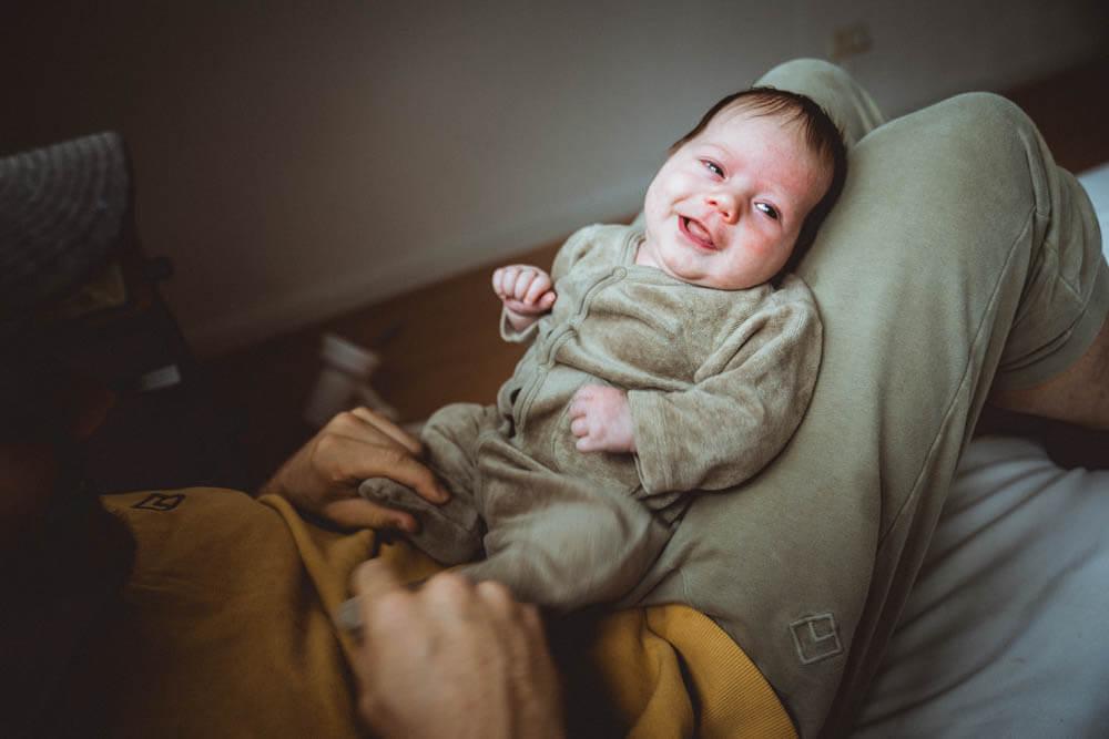Papa spielt mit Neugeborenem auf dem Schoß