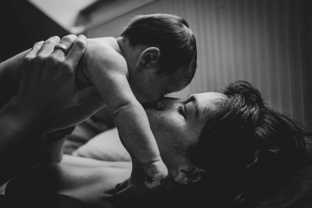 Mama hält Baby über ihrem Kopf und küsst es