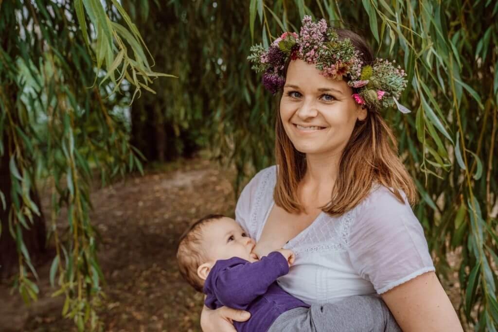 Mutter stillt Sohn unter Baum mit Blumenkranz
