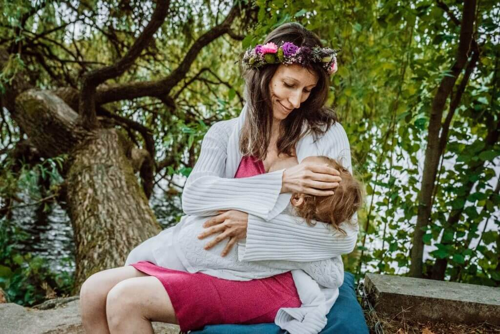 Mutter stillt Baby auf Mauer und streichelt den Kopf