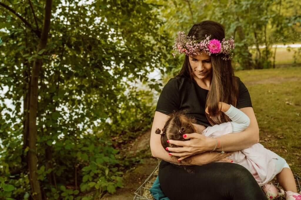 Mutter trägt Blumenkranz und stillt Kleinkind im Park