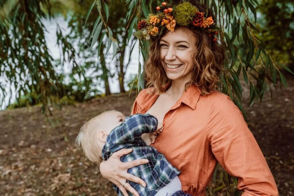 Kleinkind in Karohemd wird unter Baum gestillt