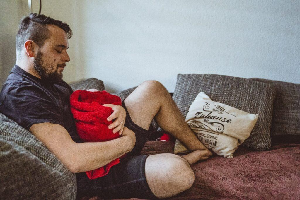 Vater hält Neugeborenes in Handtuch und weint