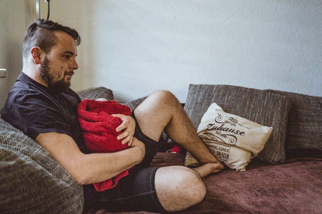 Vater sitzt auf der Couch und hält Neugeborenes