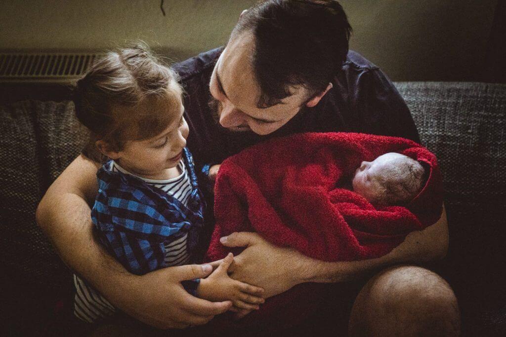 Vater hält Tochter und Neugeborenes in Arm