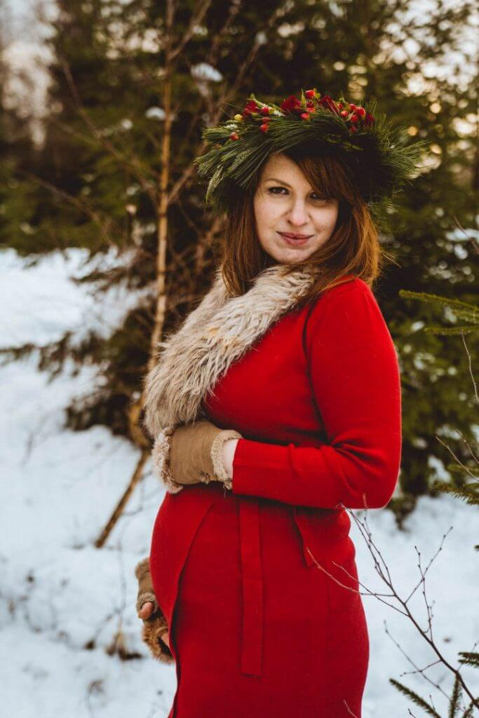Schwangere steht in verschneitem Wald und schaut in Kamera
