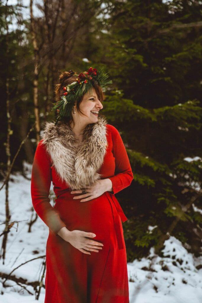 Schwangere in rotem Kleid steht im Wald und hält Bauch