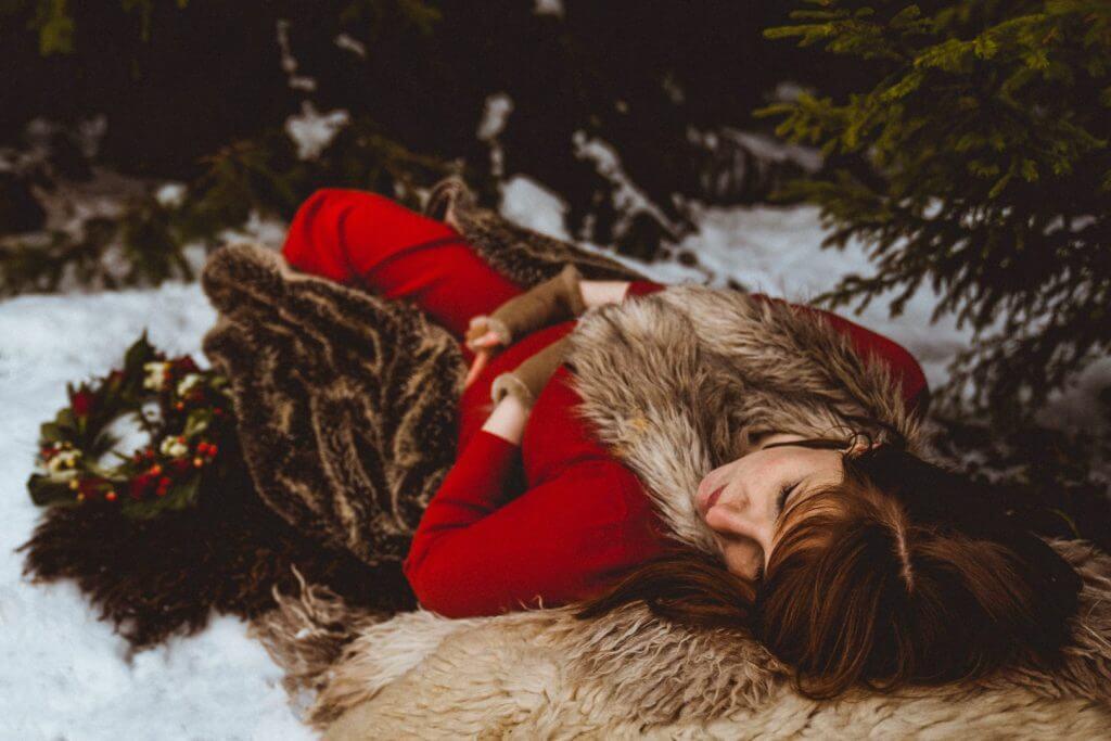 Schwangere liegt auf Pelz im Schnee