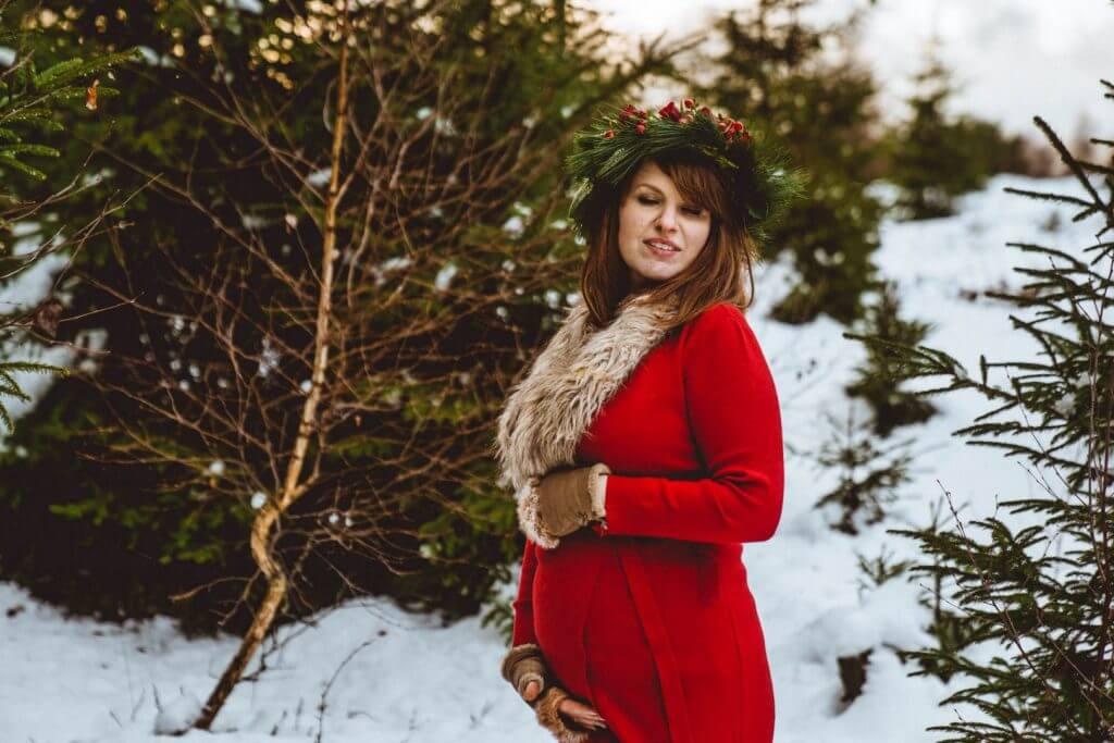 Schwangere steht im verschneiten Wald  und hält Bauch
