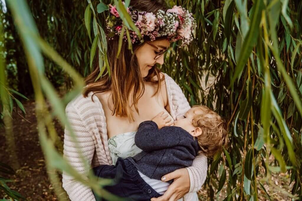 Mama stillt Kleinkind unter Baum