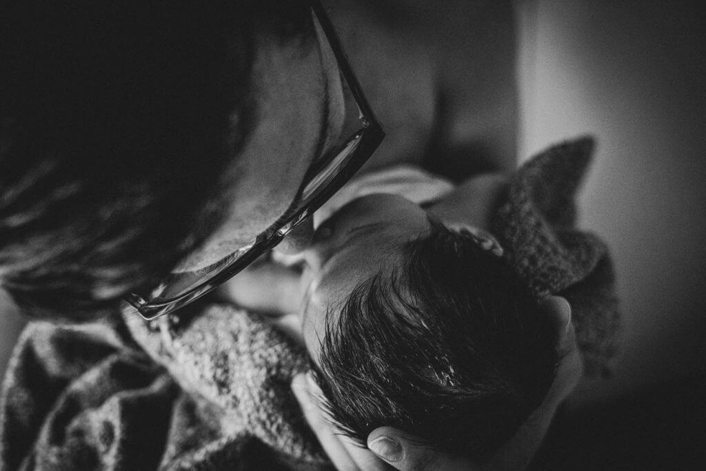 Papa gibt Neugeborenem Nasenstupser