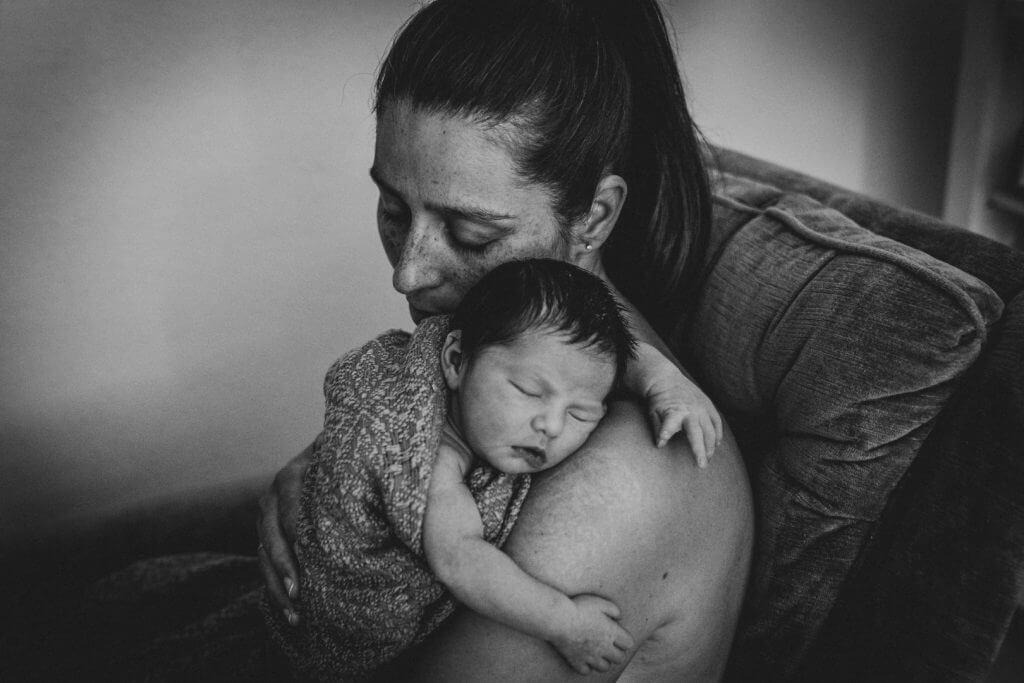 Neugeborenes schläft auf Mutters Schulter