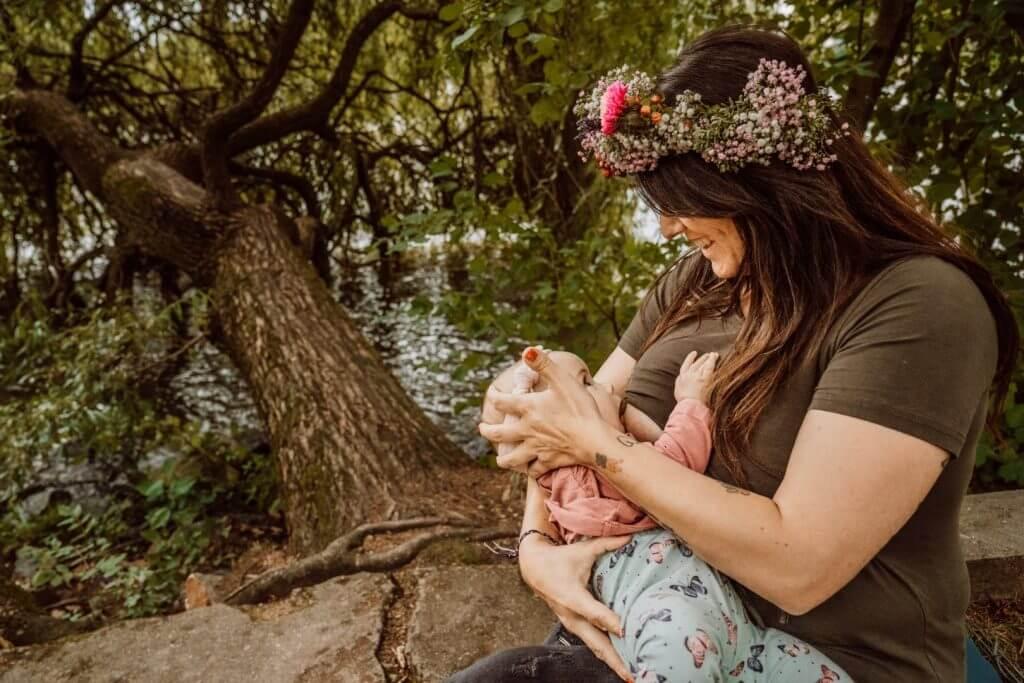 Mutter stillt Baby auf Mauerrand im Wald