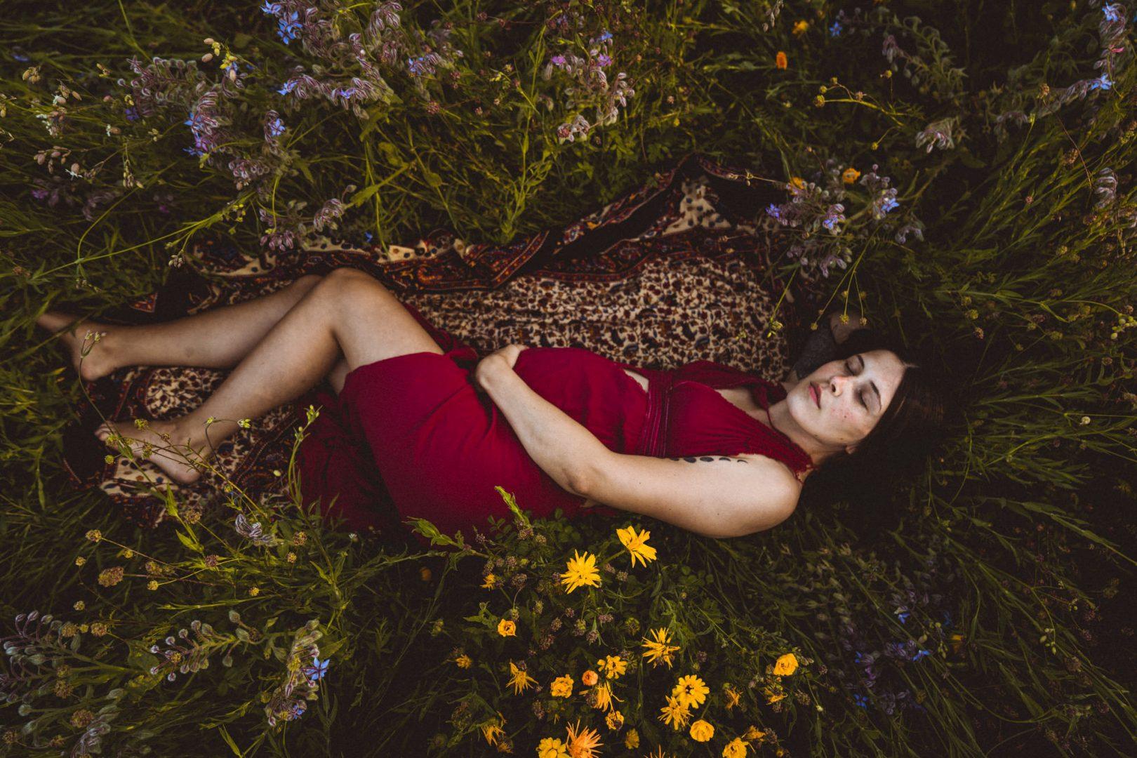 Schwangere liegt in rotem Kleid in Blumenwiese
