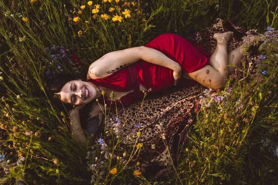 Schwangere liegt lachend in Blumenwiese