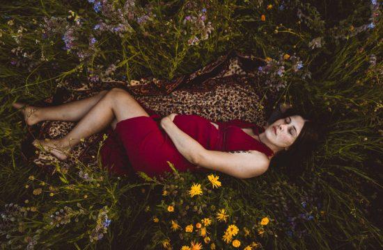 Schwangere liegt in Blumenwiese