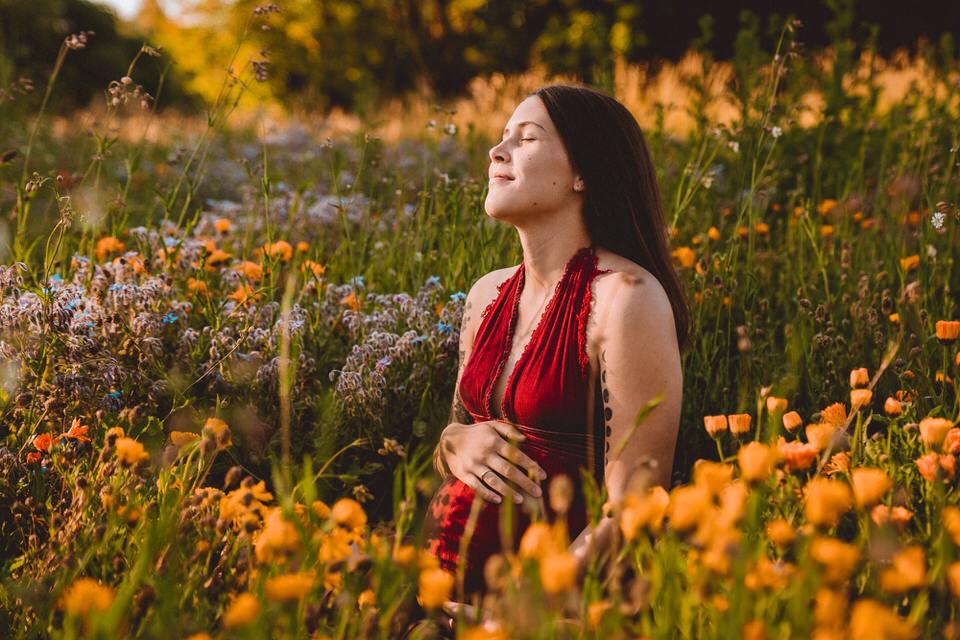 Schwangere sitzt lächelnd in Wildblumenwiese