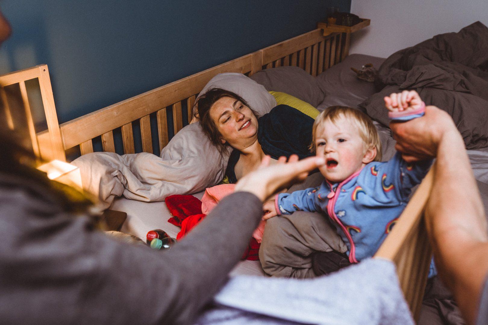 Kleinkind spielt im Familienbett