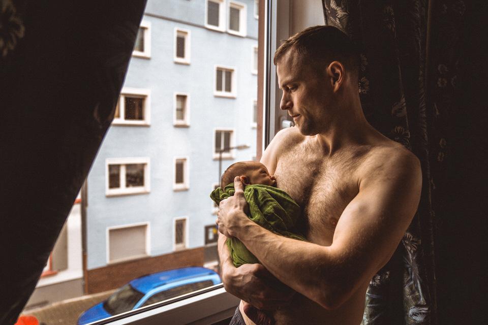 Vater kuschelt Baby am Fenster