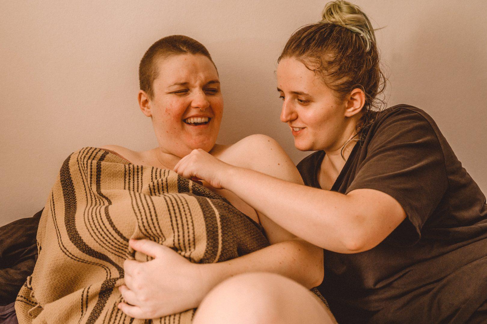 Mutter lacht nach Hausgeburt und zeigt Baby ihrer Schwester