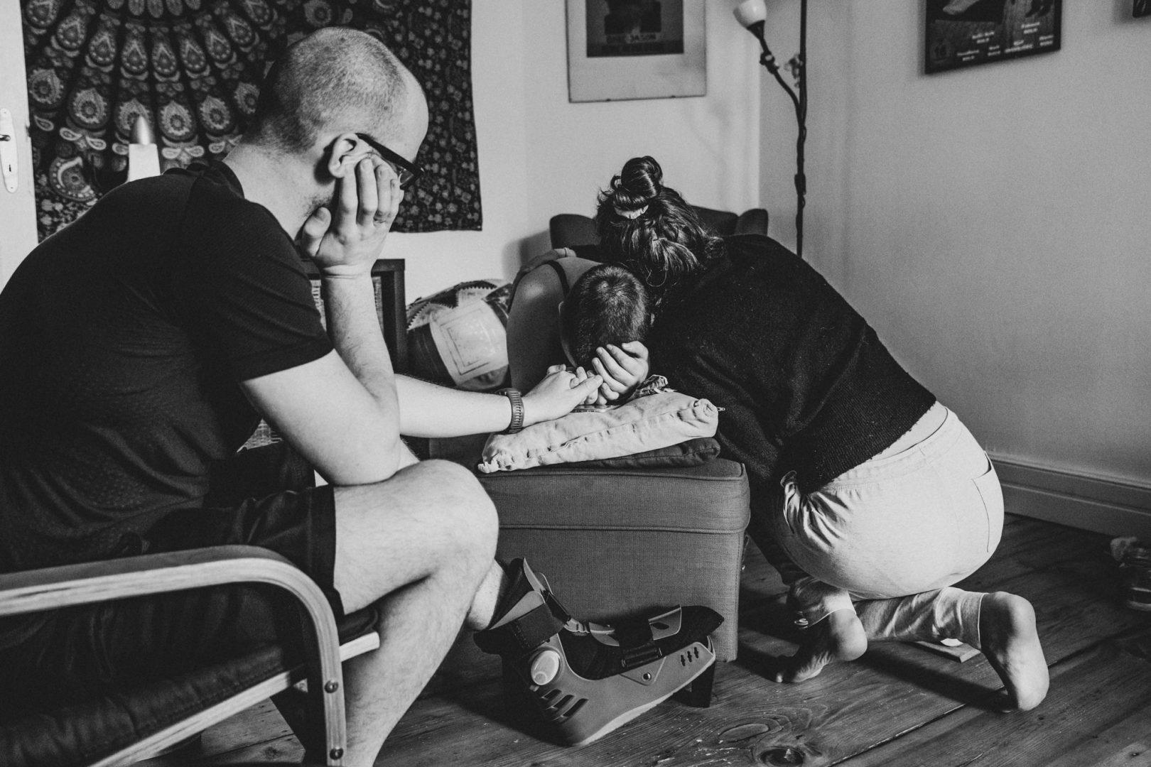 Hebamme umarmt Gebärende während Hausgeburt